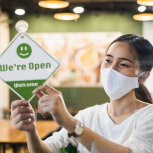 """Woman holding a """"we're open"""" sign"""